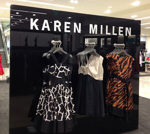 Black Back Painted Glass with sign - Karen Millen and dresses hanging on racks in front