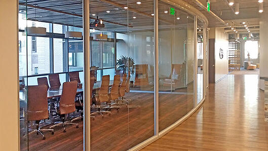 Curved glass office with hardwood floors