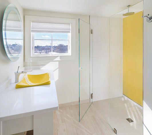 Bathroom with yellow back painted glass and clear glass shower door