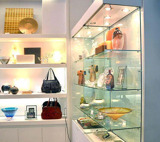 Retail glass shelves with boutique products and handbags sitting on top