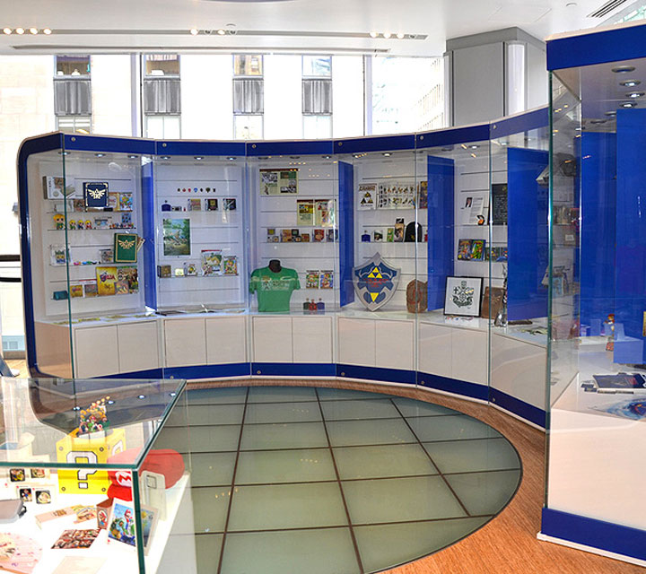 Curved glass display cases with blue accents in brightly lit retail showroom