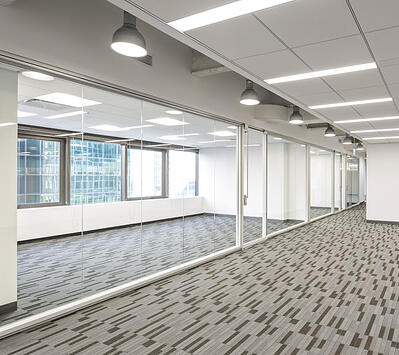 Full glass office in brightly lit office building floor