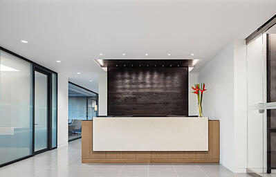 Reception desk next to office with glass office walls