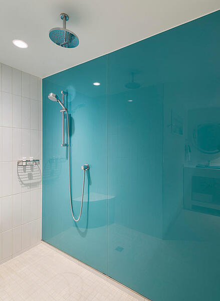 Shower with glass door and turquoise back painted glass