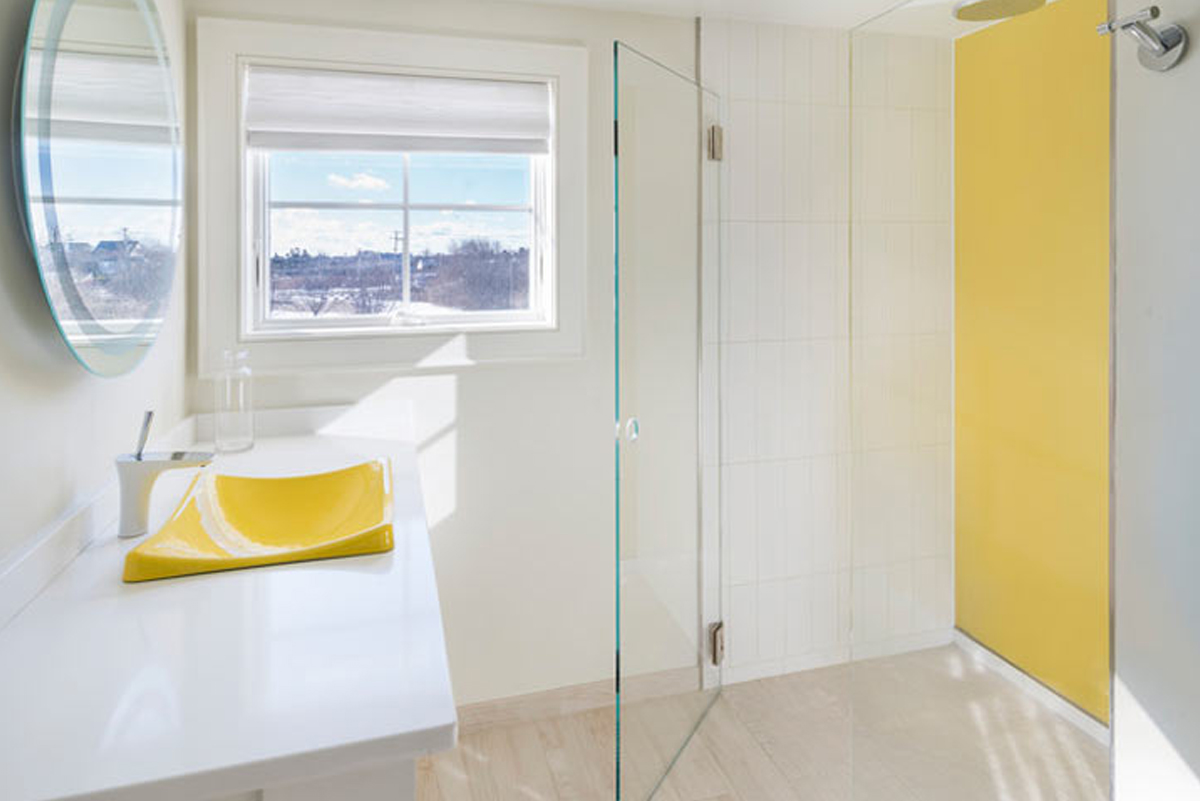 Yellow decorative glass on bathroom shower wall and sink