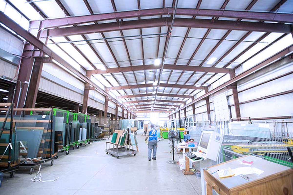 Wide view of Warehouse with workers and palletes of glass